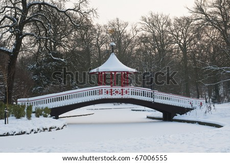 Japanese ornamental bridge in winter with snow and ice - stock photo