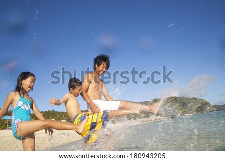 Japanese parent-child playing in the water at the beach