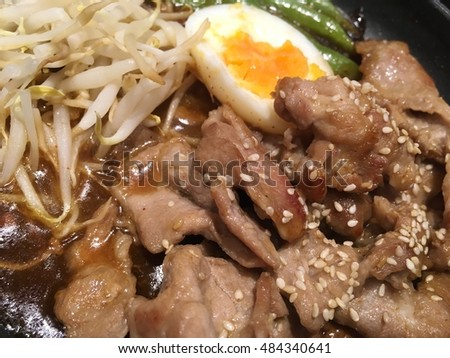 Japanese pork food with egg and sauce on black plate