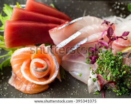 Japanese raw fish on black plate. Also known as Sashimi. - stock photo