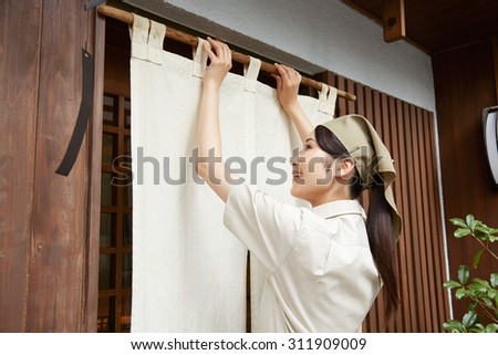 Japanese restaurant clerk hanging the noren - stock photo
