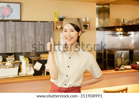 Japanese restaurant clerk thumbs up gesture - stock photo