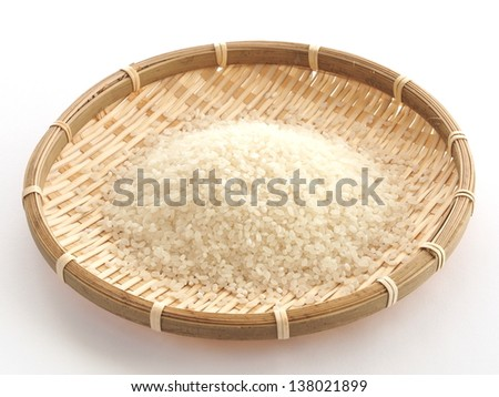 Japanese rice grains on bamboo basket - stock photo
