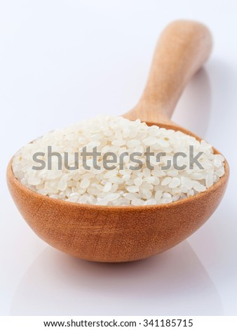 Japanese rice, the short rice used for sushi in wooden spoon with selective focus. - stock photo