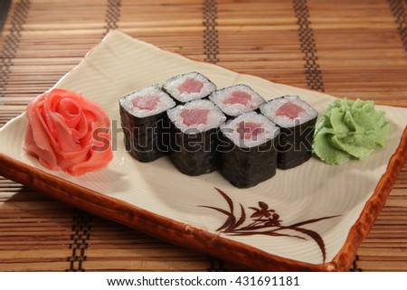 Japanese roll with wasabi sauce on plate with fish - stock photo