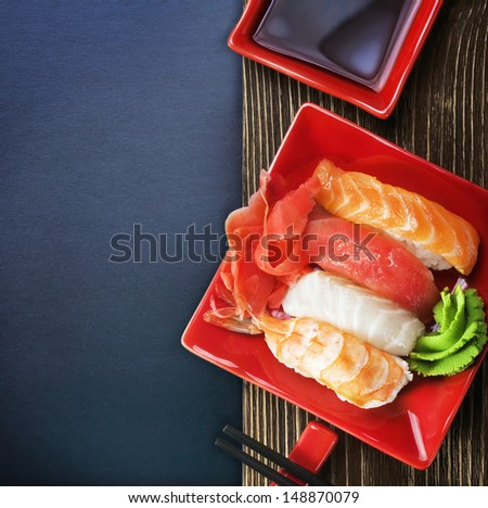 Japanese seafood sushi and chopstick on a black background for text - stock photo