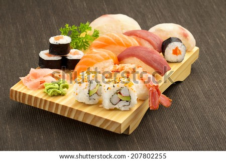 japanese seafood sushi and maki on wooden plate - stock photo