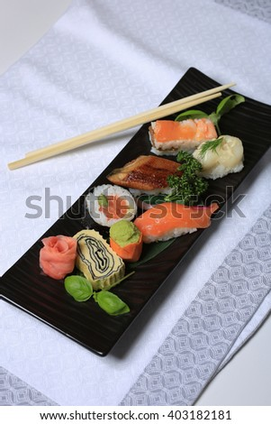Japanese seafood sushi , rolls and chopstick on a white plate  - stock photo