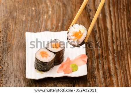 Japanese shushi roll in chopsticks on wood