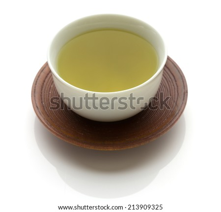 Japanese simmered green tea in a ceramic cup on a traditional wooden saucer isolated on white with copy space  - stock photo