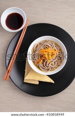 Japanese soba noodle soup and roasted tofu - stock photo