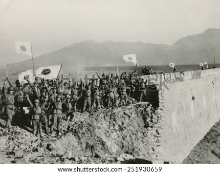 Japanese soldiers celebrate the capture of Nanking, China. A detachment of Japanese troops on the high wall of Nanking give a Bauzai salute. Flags of Japan is waved in victory. Ca. Dec. 13-31, 1937. - stock photo