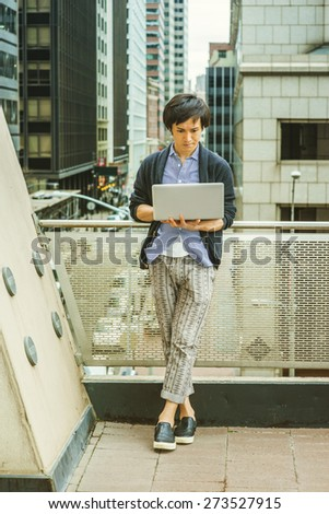 Japanese student studying in New York. Wearing patterned shirt, black sweater, casual pants, leather shoes, a young guy standing by railing in business district, reading, working on laptop computer.  - stock photo