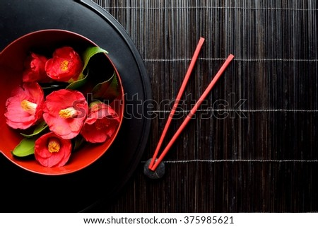 """Japanese style flower arrangement """"Japanese camellia"""" with red chopsticks on the black tray - stock photo"""