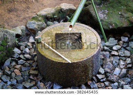 """Japanese style traditional bamboo fountain at Ryoan-ji temple in Kyoto, Japan. On the surface of basin, consisted four Chinese characters called """"Tsukubai"""". It mean """"I learn only that I am contented"""". - stock photo"""