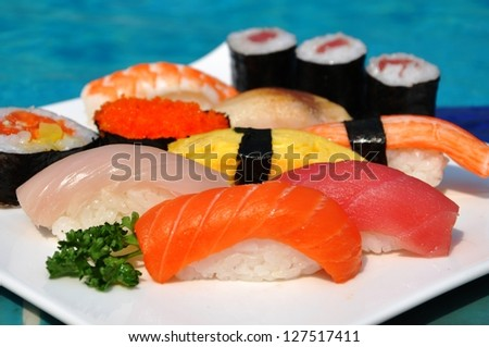 Japanese sushi and sashimi on a white plate in front of the pool. - stock photo