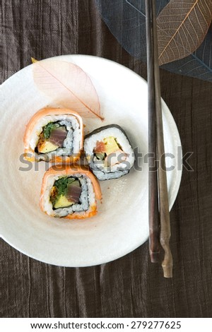 japanese sushi dish with colorful dried leaves decoration - stock photo