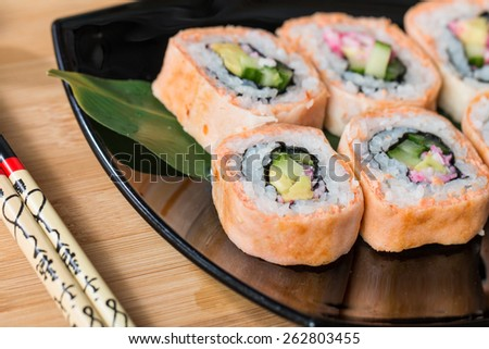 Japanese sushi rolls served on black plate - stock photo