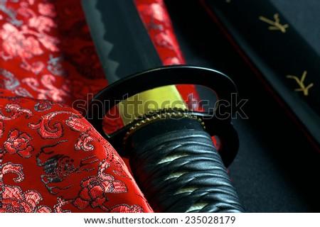 Japanese sword katana on satin background - stock photo