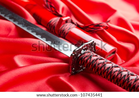 Japanese sword takana on red satin background - stock photo