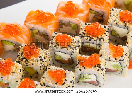 Japanese tasty sushi set on a white plate over black background - stock photo