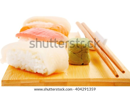 Japanese traditional cuisine - Different Types of Nigiri Sushi : Tuna (maguro) Salmon (sake) and Eel (unagi) with Wasabi  and chopstick on wooden plate isolated over white background - stock photo