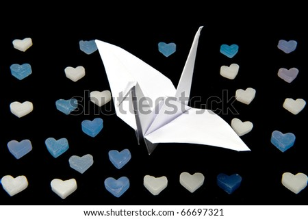 Japanese traditional origami paper crane with heart shape candle isolated on black - stock photo