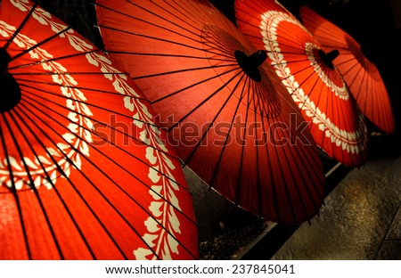 Japanese traditional red umbrellas with with floral motives - stock photo