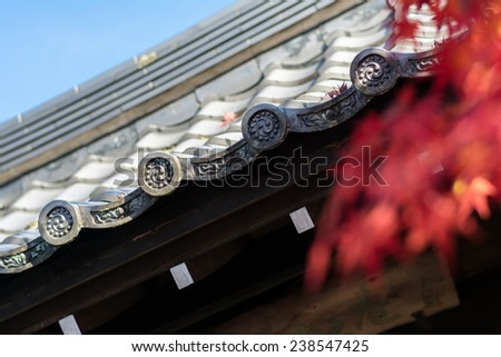 Japanese traditional temple roof under Autumn season ambiance - stock photo