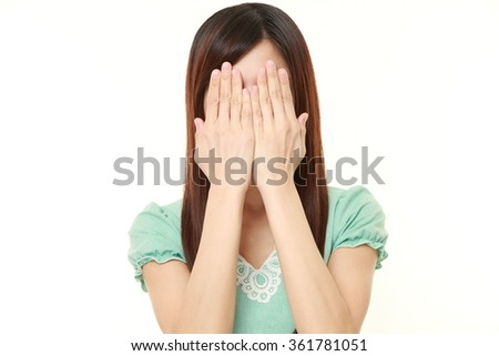 Japanese woman covering her face with hands - stock photo