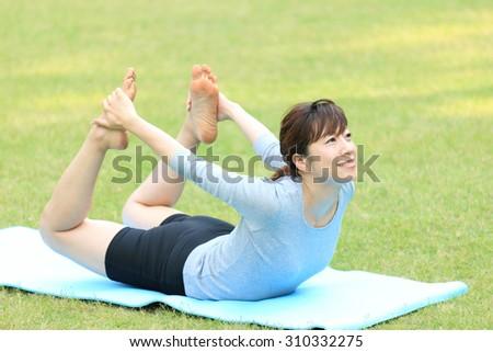 Japanese woman doing yoga bow pose - stock photo