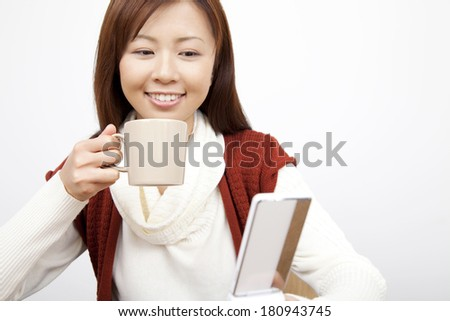 Japanese woman drinking coffee while looking at the mail on mobile phone