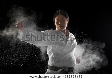 Japanese woman giving a hit to the punching bag - stock photo