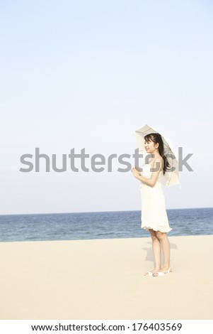 Japanese woman holding an umbrella on the beach