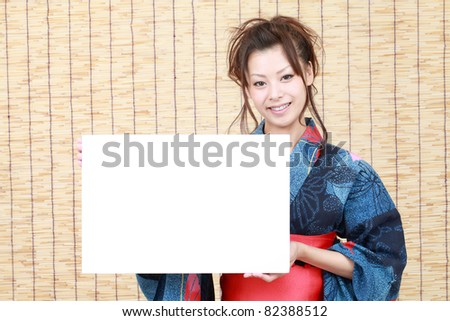 Japanese woman in traditional clothes of Kimono with billboard - stock photo