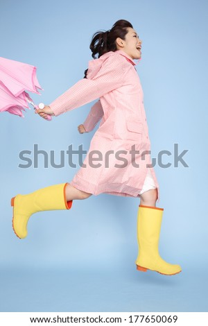 Japanese woman jumping wearing rain gear