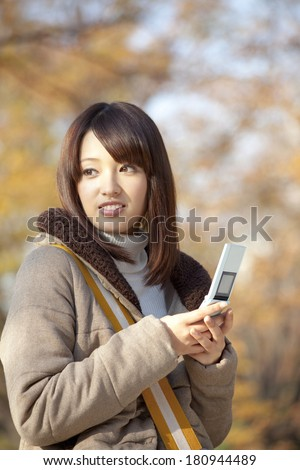 Japanese woman looking back, with a mobile phone on her hand,