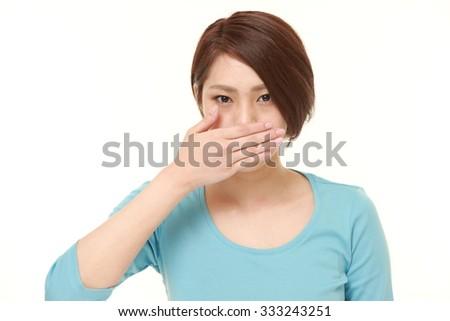 Japanese woman making the speak no evil gesture - stock photo