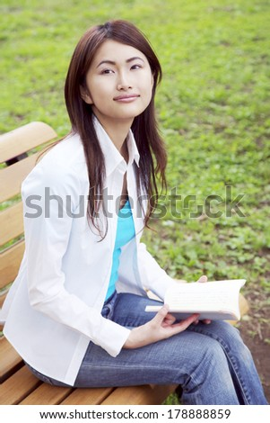 Japanese woman reading on a bench