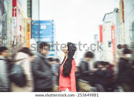 japanese woman standing in the crowd in tokyo city center. she looks amazed at the buildings - stock photo