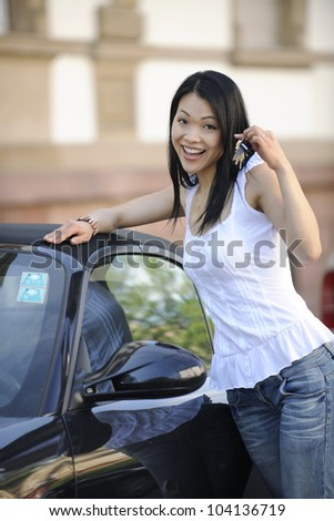 japanese woman with her new car showing keys