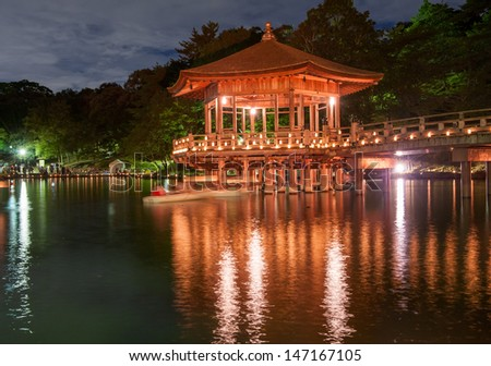 Japanese wooden gazebo is shortly after the sunset reflecting in the water. Nara, Japan. - stock photo