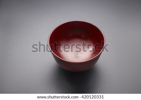 Japanese wooden red bowl on black background.                                  - stock photo