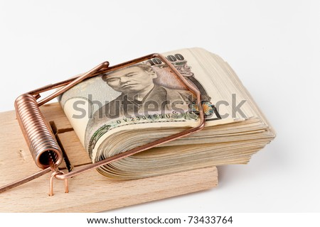 Japanese yen bills in a mousetrap. Japanese money - stock photo