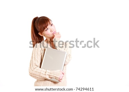Japanese young woman with laptop computer thinks about something