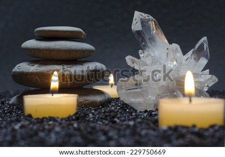 japanese ZEN garden in black sand with stacked stones, crystal and candle lights - stock photo