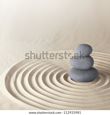 Japanese zen garden meditation stone for concentration and relaxation sand and rock for harmony and balance in pure simplicity - stock photo