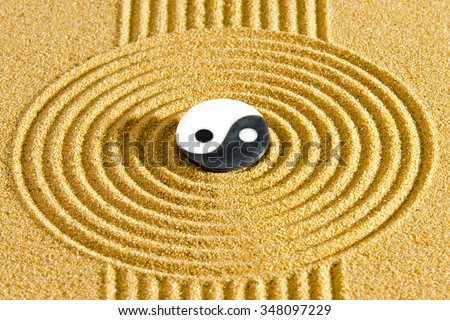 Japanese ZEN garden with textured sand and stone with yin yang symbol - stock photo