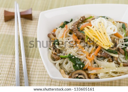 Japchae - Stir fried Korean sweet potato noodles with vegetables, mushrooms and beef garnished with slices of fried egg and sesame seeds. - stock photo