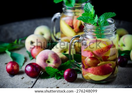 Jar delicious refreshing drink of peach fruits and plum  with mint on wooden, infused water - stock photo
